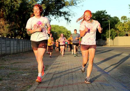 rustenburg: Rustenburg Marathon Club Rainbow Run - NOVEMBER 25: Two Chearful running young girls covered with powder paint at colour run on November 25, 2015, Rustenburg, South Africa.