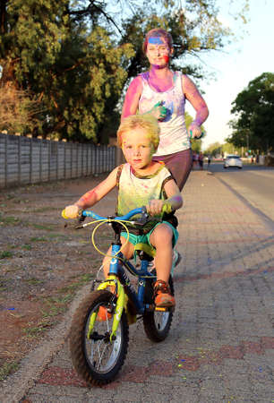 rustenburg: Rustenburg Marathon Club Rainbow Run - NOVEMBER 25: Mom and son on bicycle covered with powder paint at colour run on November 25, 2015, Rustenburg, South Africa.