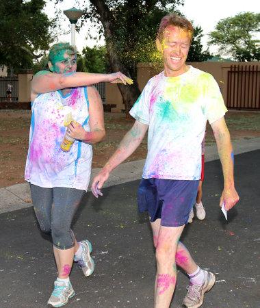 rustenburg: Rustenburg Marathon Club Rainbow Run - NOVEMBER 25: Woman throwing husband with yellow powder paint at colour run on November 25, 2015, Rustenburg, South Africa. Editorial