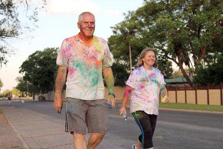 rustenburg: Rustenburg Marathon Club Rainbow Run - NOVEMBER 25: Old couple walking covered with powder paint at colour run on November 25, 2015, Rustenburg, South Africa. Editorial