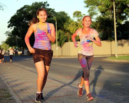 rustenburg: Rustenburg Marathon Club Rainbow Run - NOVEMBER 25: Two Chearful running teen girls covered with powder paint at colour run on November 25, 2015, Rustenburg, South Africa.