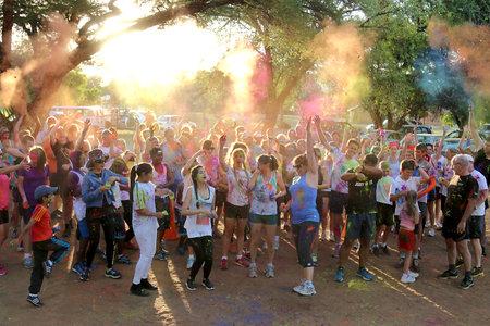 rustenburg: Rustenburg Marathon Club Rainbow Run - NOVEMBER 25: Crowd of runners throwing powder paint into air at start of colour run on November 25, 2015, Rustenburg, South Africa. Editorial