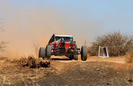 Sun City, South Africa - OCTOBER 1, 2016: Front view close-up of red Aceco rally car at road crossing in race at Sun City 450 Rally Racing event, Sun City, South Africa