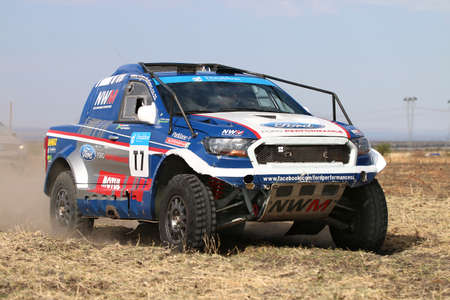 off road racing: Sun City, South Africa - OCTOBER 1, 2016: Forty Five degree close-up view of Speeding  white and blue Ford Ranger rally car in race at Sun City 450 Rally Racing event, Sun City, South Africa