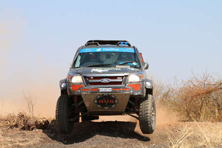 Sun City, South Africa OCTOBER 1, 2016: Front view close-up of black Ford Ranger rally car ramping down slope in race at Sun City 450 Rally Racing event, Sun City, South Africa
