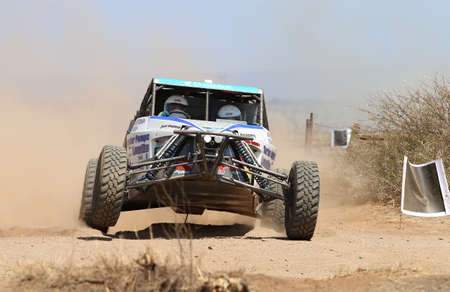 Sun City, South Africa OCTOBER 1, 2016: Front view close-up of white Chenowth rally car pull away at road crossing in race at Sun City 450 Rally Racing event, Sun City, South Africa