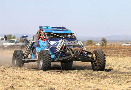 off road racing: Sun City, South Africa - OCTOBER 1, 2016: Forty Five degree close-up view of Speeding Blue Bat Spec 0 rally car in race at Sun City 450 Rally Racing event, Sun City, South Africa