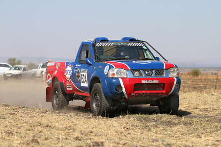 Sun City, South Africa - OCTOBER 1, 2016: Forty Five degree close-up view of Speeding red and blue Toyota Nissan single cab rally car in race at Sun City 450 Rally Racing event, Sun City, South Africa Editorial