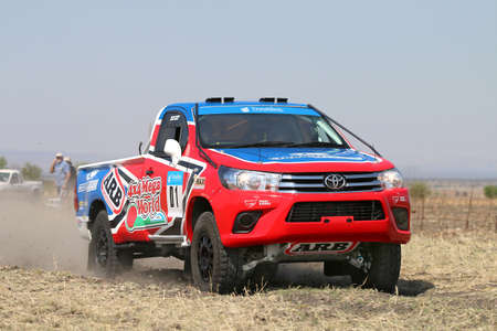 Sun City, South Africa - OCTOBER 1, 2016: Forty Five degree close-up view of Speeding red and blue Toyota Hilux single cab rally car in race at Sun City 450 Rally Racing event, Sun City, South Africa