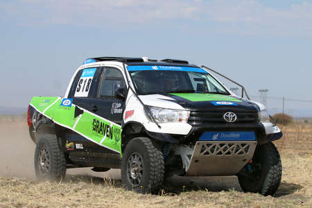 off road racing: Sun City, South Africa - OCTOBER 1, 2016: Forty Five degree close-up view of Speeding green and white Toyota Hilux twin cab rally car in race at Sun City 450 Rally Racing event, Sun City, South Africa