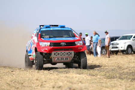 off road racing: Sun City, South Africa - OCTOBER 1, 2016: Front view of Speeding red and blue Toyota Hilux twin cab rally car in race at Sun City 450 Rally Racing event, Sun City, South Africa