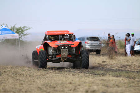 off road racing: Sun City, South Africa � OCTOBER 1, 2016: Front view of Speeding orange Bat rally car in race at Sun City 450 Rally Racing event, Sun City, South Africa