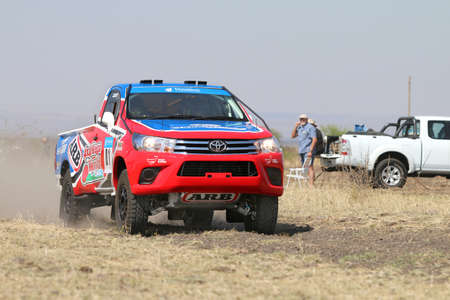 Sun City, South Africa – OCTOBER 1, 2016: Forty Five degree close-up view of Speeding red and blue Toyota Hilux single cab rally car in race at Sun City 450 Rally Racing event, Sun City, South Africa