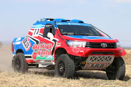 Sun City, South Africa - OCTOBER 1, 2016: Forty Five degree close-up view of Speeding red and blue Toyota Hilux twin cab rally car in race at Sun City 450 Rally Racing event, Sun City, South Africa