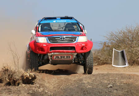 Sun City, South Africa - OCTOBER 1, 2016: Front view close-up of red and blue Toyota Hilux single cab rally car at road crossing in race at Sun City 450 Rally Racing event, Sun City, South Africa
