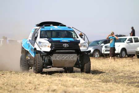 off road racing: Sun City, South Africa - OCTOBER 1, 2016: Front view of Speeding white and blue Toyota Hilux twin cab rally car in race at Sun City 450 Rally Racing event, Sun City, South Africa Editorial
