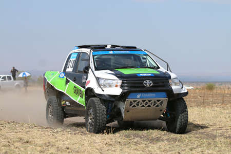 Sun City, South Africa - OCTOBER 1, 2016: Forty Five degree close-up view of Speeding green and white Toyota Hilux twin cab rally car in race at Sun City 450 Rally Racing event, Sun City, South Africa