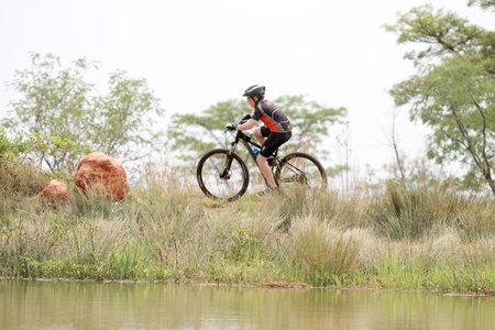 rustenburg: Rustenburg, South Africa - OCTOBER 23, 2016: Young boy riding on edge of dam at Mathaithai Mountain Bike Race, Rustenburg, South Africa.