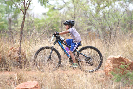 Rustenburg, South Africa - OCTOBER 23, 2016: Young Inian boy riding through bush at Mathaithai Mountain Bike Race, Rustenburg, South Africa.