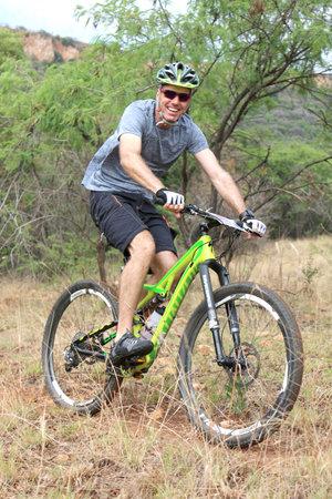 Rustenburg, South Africa - OCTOBER 23, 2016: Smiling man enjoying outdoors ride at Mathaithai Mountain Bike Race, Rustenburg, South Africa. Editorial