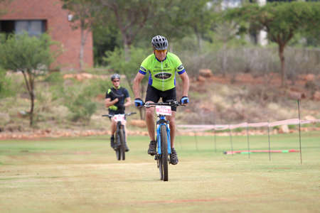 rustenburg: Rustenburg, South Africa - OCTOBER 23, 2016: Middle aged man chasing to the finish line at the Mathaithai Mountain Bike Race, Rustenburg, South Africa.