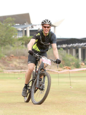 Rustenburg, South Africa - OCTOBER 23, 2016: Happy middle aged man riding to the finish line at the Mathaithai Mountain Bike Race, Rustenburg, South Africa.