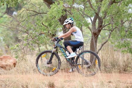 rustenburg: Rustenburg, South Africa - OCTOBER 23, 2016: Young Inian girl riding through bush at Mathaithai Mountain Bike Race, Rustenburg, South Africa.