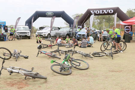 rustenburg: Rustenburg, South Africa - OCTOBER 23, 2016: Abandoned Bicycles on grass in front of luxury 4x4 motor car display at finish line at the Mathaithai Mountain Bike Race, Rustenburg, South Africa. Editorial