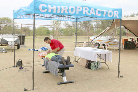 rustenburg: Rustenburg, South Africa - OCTOBER 23, 2016: Chiropractor assisting cyclist at finish line at the Mathaithai Mountain Bike Race, Rustenburg, South Africa.