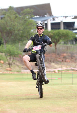 Rustenburg, South Africa - OCTOBER 23, 2016: Happy middle aged man popping wheelie at the finish line at the Mathaithai Mountain Bike Race, Rustenburg, South Africa. Editorial