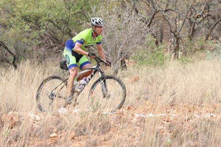 rustenburg: Rustenburg, South Africa - OCTOBER 23, 2016: Middle Aged man riding through bush at Mathaithai Mountain Bike Race, Rustenburg, South Africa. Editorial