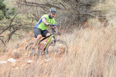 rustenburg: Rustenburg, South Africa - OCTOBER 23, 2016: Middle aged man riding through bush at Mathaithai Mountain Bike Race, Rustenburg, South Africa.