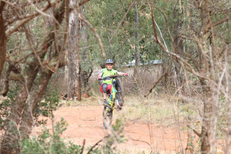 wheelie: Rustenburg, South Africa - OCTOBER 23, 2016: Young man showing off by popping wheelie at Mathaithai Mountain Bike Race, Rustenburg, South Africa.