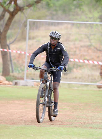 Rustenburg, South Africa - OCTOBER 23, 2016: Middle aged black African man riding to the finish line at the Mathaithai Mountain Bike Race, Rustenburg, South Africa. Editorial
