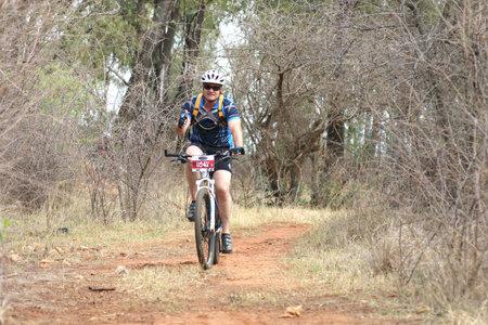 rustenburg: Rustenburg, South Africa - OCTOBER 23, 2016: Middle aged man enjoying outdoors ride at Mathaithai Mountain Bike Race, Rustenburg, South Africa. Editorial