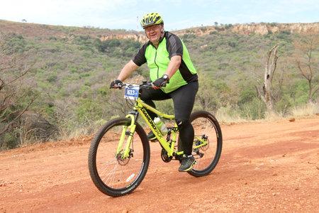 Rustenburg, South Africa - OCTOBER 23, 2016: Smiling aged man enjoying outdoors ride at Mathaithai Mountain Bike Race, Rustenburg, South Africa.