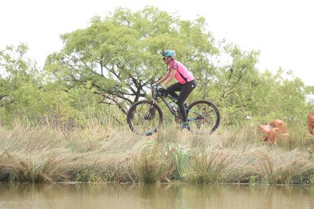rustenburg: Rustenburg, South Africa - OCTOBER 23, 2016: Young woman riding on edge of dam at Mathaithai Mountain Bike Race, Rustenburg, South Africa.