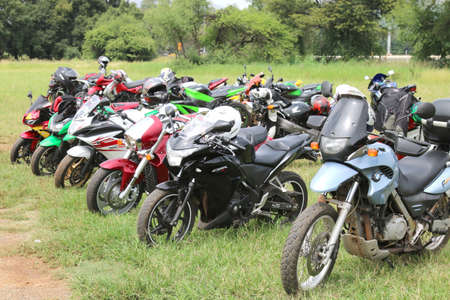 Rustenburg, South Africa - March 3, 2017: Rows of colourful parked motorbikes on green grass at Yearly Mass Ride of Tainted Souls Motorbike Club, Rustenburg, South Africa.