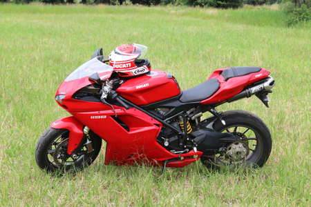 Rustenburg, South Africa - March 3, 2017: Parked red Ducati 1198 motorbike on green grass at Yearly Mass Ride of Tainted Souls Motorbike Club, Rustenburg, South Africa. Editorial