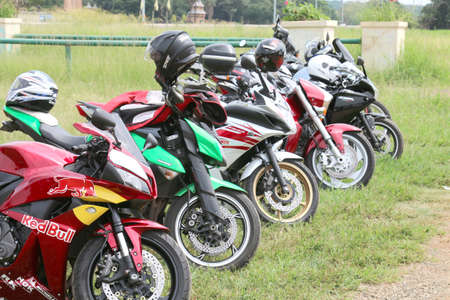 Rustenburg, South Africa - March 3, 2017: Row of colourful parked motorbikes on green grass at Yearly Mass Ride of Tainted Souls Motorbike Club, Rustenburg, South Africa.