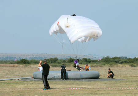 RUSTENBURG, SOUTH AFRICA - April 28, 2017: National Skydiving Championships. Jumper with white open parachute landing on target during Classic Accuracy event.