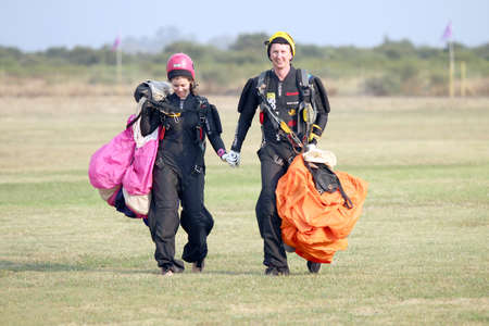 RUSTENBURG, SOUTH AFRICA - April 28, 2017: National Skydiving Championships. Love is in the air! Man and woman skydivers walking hand in hand after successful landings