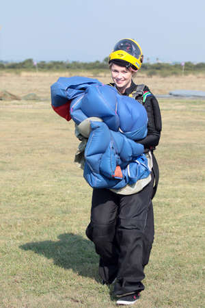 RUSTENBURG, SOUTH AFRICA - April 28, 2017: National Skydiving Championships. Attractive female sky diver posing with bright blue parachute and yellow helmet after safe landing.