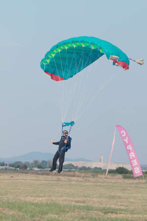 RUSTENBURG, SOUTH AFRICA - April 28, 2017: National Skydiving Championships. Male skydiver coming in for landing on grass with open green parachute.