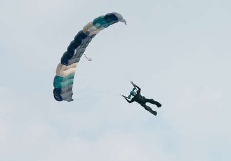 RUSTENBURG, SOUTH AFRICA - April 28, 2017: National Skydiving Championships. Male sky diver with brightly coloured open parachute gliding in sideways for landing Editorial