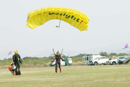 RUSTENBURG, SOUTH AFRICA - April 28, 2017: National Skydiving Championships. Masked skydiver coming in for landing on grass with open bright yellow parachute.