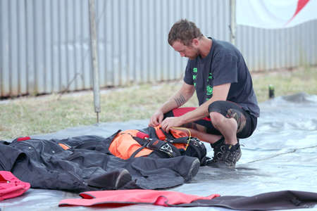 sequences: RUSTENBURG, SOUTH AFRICA - April 28, 2017: National Skydiving Championships. Skydiver packing and checking chute before next jump.