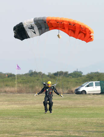 RUSTENBURG, SOUTH AFRICA - April 28, 2017: National Skydiving Championships. Male skydiver making safe landing landing on grass with open bright colourful parachute. Editorial