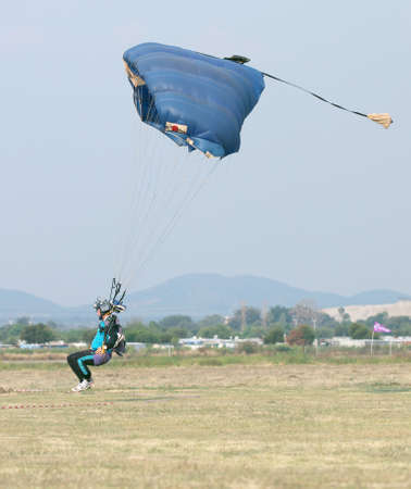 RUSTENBURG, SOUTH AFRICA - April 28, 2017: National Skydiving Championships. Male skydiver coming in for fast landing on grass (Landing Series Image 1 of 4).