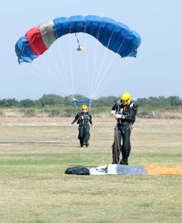 RUSTENBURG, SOUTH AFRICA - April 28, 2017: National Skydiving Championships. Female skydiver making safe landing on grass with open brightly colourful parachute.